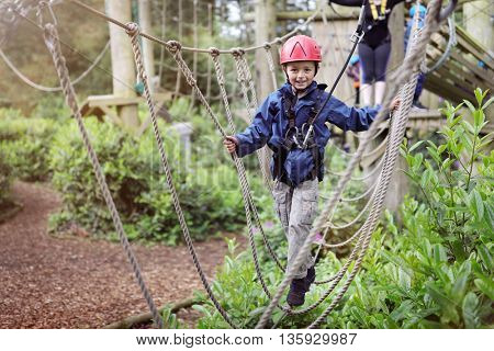 Boy in a harness on a treetop adventure park walking across a rope bridge