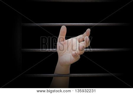 closeup on hands of man sitting in jail.