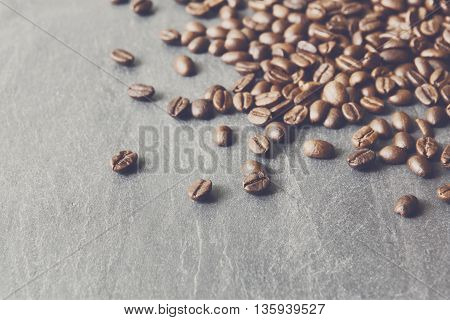 Closeup of coffee beans on grey stone surface. Heap of roasted coffee bean on stone texture with copy space. Coffee shop or cafe background. Natural stone and seeds. Soft color toning