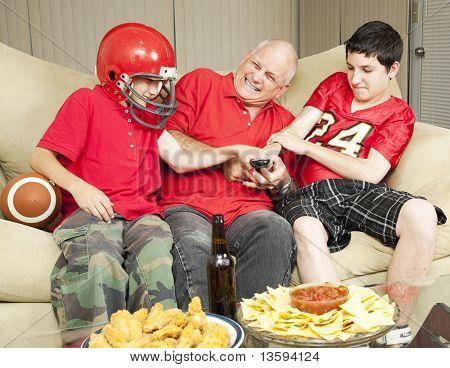 American Football Fans-Vater und Söhne - kämpfen für die TV-Fernbedienung.