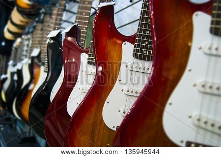 electric guitars hanging in a row in a music store