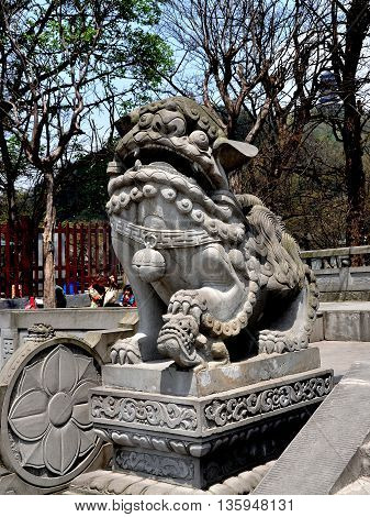 Dujiangyan China - April 8,  2011: Carved stone statue of a Chinese Fu dog stands on a terrace overlooking the Min River