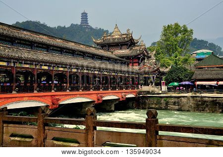 Dujiangyan China - October 9 2013: Ming Dynasty Nan Qiao covered bridge over the Min River with distant hilltop pagoda