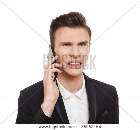 Businessman calling cell phone with angry facial expression, isolated on white. Disgusted annoyed man in suit talking on mobile. Quarreling and communication problem concept, emotional male portrait.