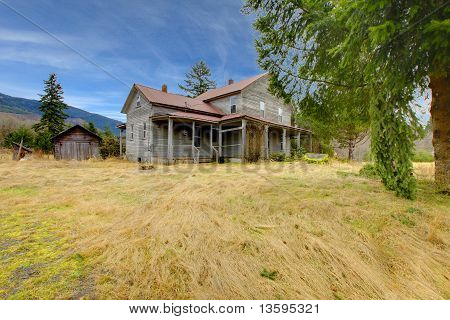 Very Old Rustic Grey House On The Country Farm Land.