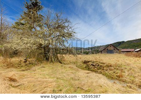 Country Farm Landscpae With Large Barn And Mountains