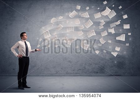 Caucasian businessman holding newspapers, which are floating away from his hands