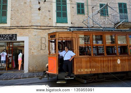 MALLORCA SPAIN - JUNE 2: The tram is on street of Soller town and tourists are in outdoor restaurant on June 2 2015 in Mallorca Spain. Up to 60 mln tourists is expected to visit Spain in year 2015.