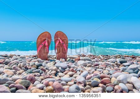 Pair of flip flops on pebble beach. Rhodes Greece