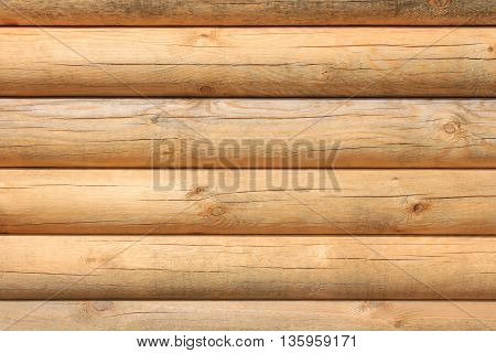 Horizontal parallel large new wooden logs in sunlight close-up and detailed