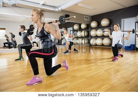 Young Friends Lifting Barbells In Gym