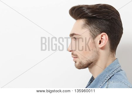 Profile of handsome young man injeans shirt posing over white background. Male with modern hairstyle in studio. Hairdressing concept.
