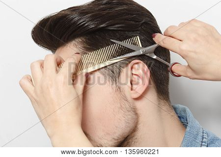 Closeup portrait of handsome young man having haircut in studio. Hairdresser cutting man'shair with scissors over white background.