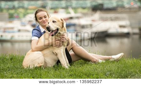 Portrait of a woman with her beautiful dog lying outdoors on green grass near river