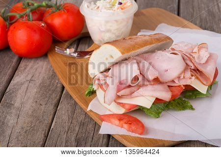 Ham sandwich with cheese tomato and lettuce on a baguette