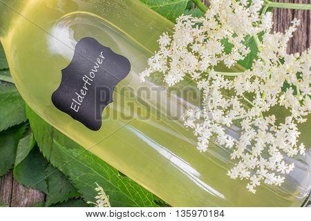 Detail of a Lying Bottle of Elderflower Syrup with Elderflower on Old Wooden Table