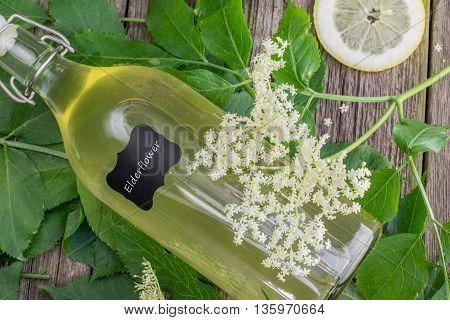 Lying Bottle of Elderflower Syrup with Elderflower and Lemon on Old Wooden Table