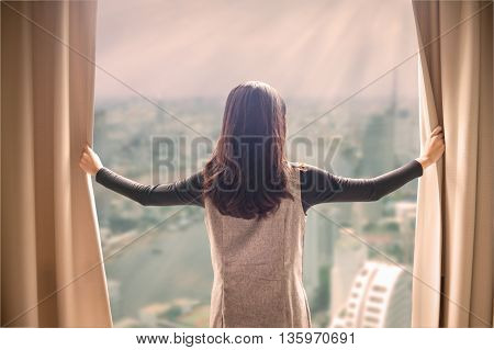Asian portrait beautiful woman opening curtains and building cityscape background