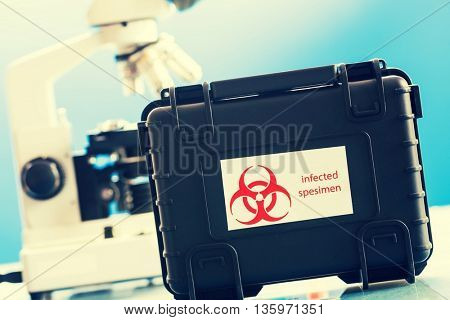Safe case with epidemiologically dangerous viruses coronavirus and microscope in laboratory
