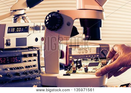 Microelectronics laboratory with the measuring instruments and microscopes. Electronic circuit board in hand