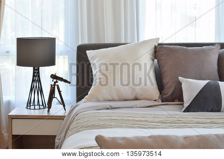 Stylish Bedroom Interior Design With Brown Patterned Pillows On Bed And Decorative Table Lamp.