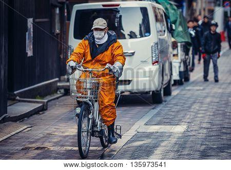 Tokyo Japan - February 27 2015: Worker rides bike on street in Akasaka district of Tokyo