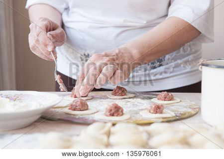 woman cooking dumplings in the bright kitchen
