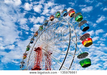 Colorful Ferris Wheel against picturesque sky on the background