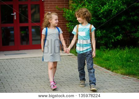 Little pupils on a schoolyard. The boy and the girl go having joined hands. Behind shoulders at school students satchels. Children look at each other and smile. Back to school.