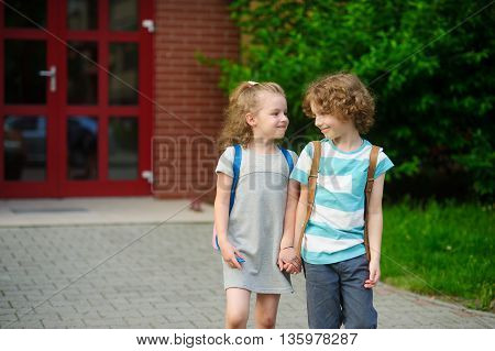 Little schoolmates on a schoolyard. The boy and the girl go having joined hands. Behind shoulders at school students satchels. Children look at each other and smile.