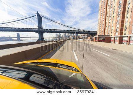 New York City yellow taxi cab driving under Manhattan Bridge