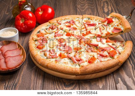Delicious pizza with ingredients served on wooden table