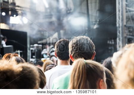 Crowd of diverse people standing watching something in the distance or queuing viewed close up from behind head and shoulders view