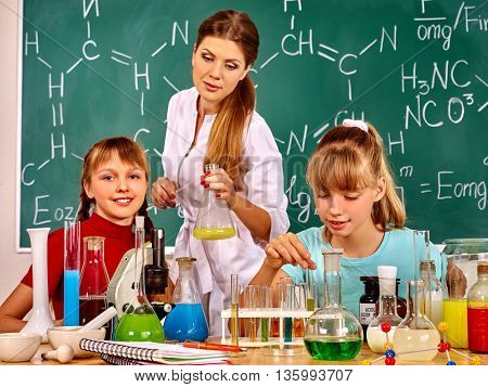 Children girl and chemistry teacher holding chemistry flask in chemistry class.