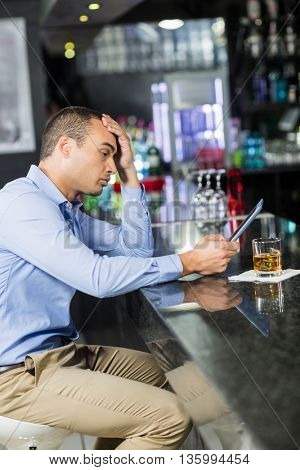 Exhausted man having a whiskey in a pub