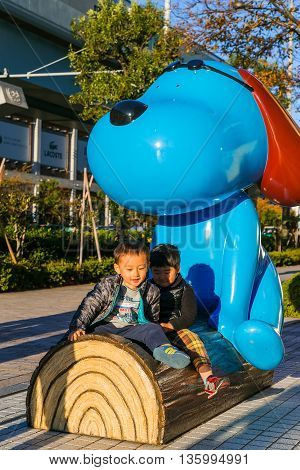 TOKYO JAPAN - NOVEMBER 27 2015: Unidentified Japanese children with a cartoon dog statue in front of Fuji Television Headquaters building in Odaiba area