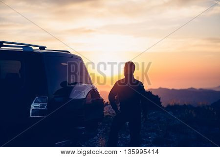 Back view of climber near car watching beautiful sundown in mountains - backlighting