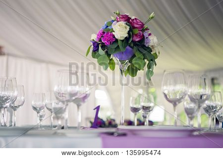 decor design round table purple lilac stripe in the middle and the white table cloth , wine glasses and glass stand vase for flowers, roses, a branch with leaves on a holiday, the wedding, the birthday party