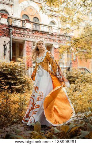 Beautiful blond woman in medieval dress walking near old building
