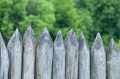 Fence stakes, a fence made of logs, tapered wooden stakes. poster