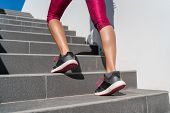 Stairs climbing running woman doing run up steps on staircase. Female runner athlete going up stairs in urban city doing cardio sport workout run outside during summer. Activewear leggings and shoes. poster
