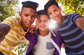 Youth culture young people group of male friends multi-ethnic teens outdoors teenagers together in park. Portrait of happy boys smiling kids looking at camera. Slow motion poster