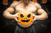 gym halloween theme gym halloween gourd bodybuilder with pumpkin in his hands, a strong man squeezes a pumpkin, sportsman's trunk, strong hands squeeze Halloween pumpkin poster