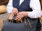 hands of an elderly woman while creating a straw bag poster
