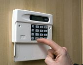 Image of a hand setting a burgler alarm poster
