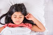 cute Indian Girl sleeping over white pillow, small asian girl sleeping on bed poster
