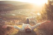Carefree happy woman lying on green grass meadow on top of mountain edge cliff enjoying sun on her face.Enjoying nature sunset.Freedom.Enjoyment.Relaxing in mountains at sunrise.Sunshine.Daydreaming poster