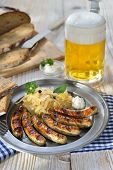 Bavarian beer garden meal - Fried sausages from Nuremberg with sauerkraut and horseradish traditionally served on a pewter plate with hearty farmhouse bread and a tankard of cold Munich lager beer poster
