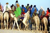 A man riding his camel behind a group of Tuareg riders on their camels poster