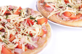 Pizzas with tomatoes, sauce, ham, sausage, cheese, dill isolated on white background